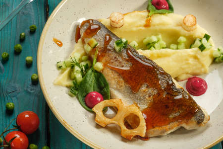 Baked sea bass with mashed potatoes vegetables and herbs Stockfoto - 136675588