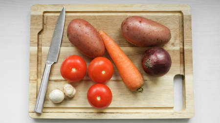 vegetables on a cutting board. Card on top of potatoes, tomato, carrots, red onions. mushrooms. The knife lies nearby.