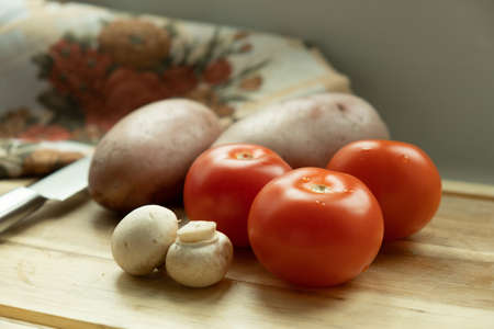 vegetables on a cutting board. Close-up of tomato, mushrooms and potatoes. And in the background is a knife.
