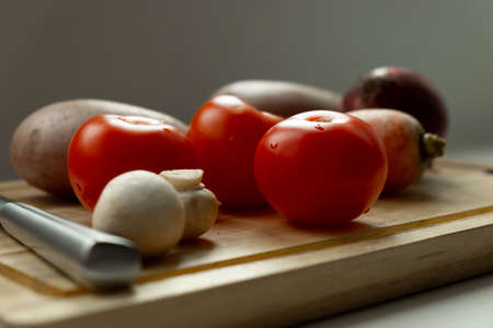 vegetables on a cutting board. Close-up of tomato, potato, mushrooms and carrots. And in the background is a knife.