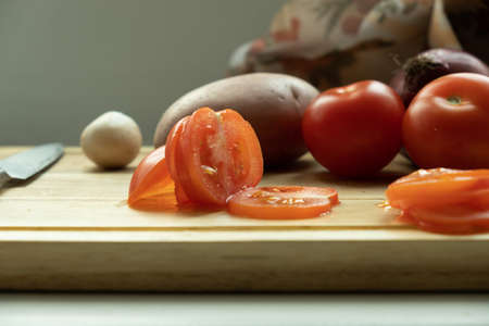 vegetables on a cutting board. close-up sliced ​​tomato, and in the background potatoes, mushrooms and carrots.