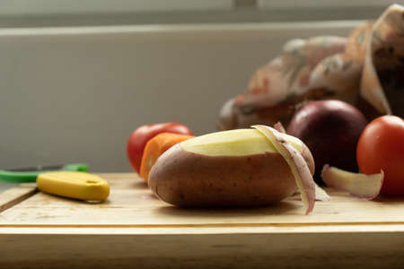 vegetables on a cutting board. close-up of peeled potatoes and in the background potatoes, carrots, red onions. The knife lies nearby.