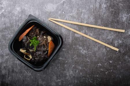 Korean dish, black mushroom salad. Top view close up. Near koreansike sticks and bibimbap