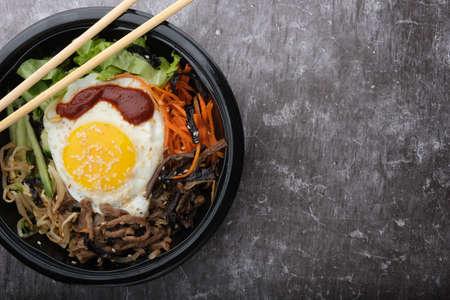 Korean dish bibimbap. Top view close up. Nearby are the Korean sticks.