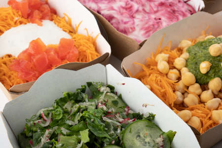 a set of different salads for vegetarians and raw foodists ready to eat in cardboard plates