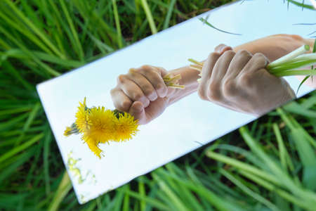 In the mirror are hands holding flower with blue sky.