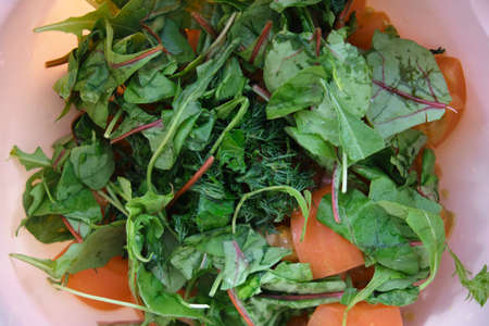 green salad in a bowl top view. close-up. amid a pink plate Stockfoto