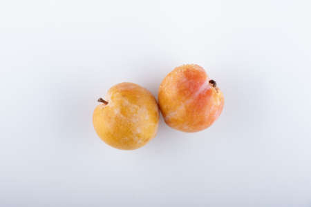 Juicy yellow plums with leaves, isolated on white background.
