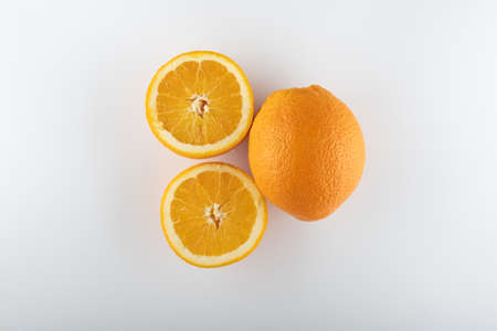 ripe oranges with sliced halves close-up on a white background