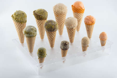 organic handmade ice cream cones in four flavors and different sizes on a stand. The flavors are chocolate, pistachio, caramel and mango. Close up