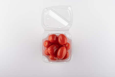 multi-colored tomatoes in a plastic box close-up on a white background