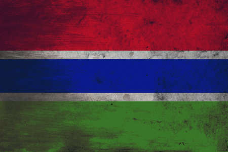 defaced: The flag of the Gambia consists of three horizontal red, blue and green bands separated by two thin white fimbriations. Adopted in 1965 to replace the British Blue Ensign defaced with the arms of the Gambia Colony and Protectorate, it has been the flag of Stock Photo