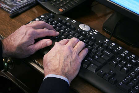 Elderly hands typing on keyboard Imagens