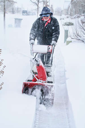 Man snow blowing during storm