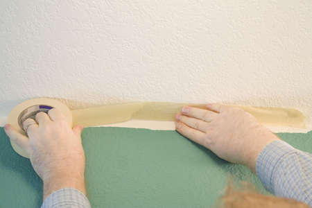Man masking off corner of wall to paint Stock Photo