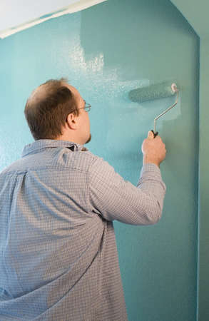 Man painting wall with roller photo