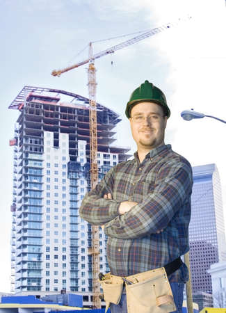 journeyman: Construction worker standing in front of a new highrise Stock Photo