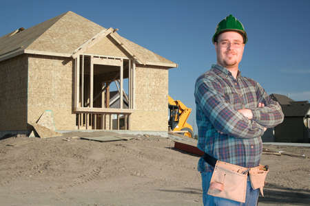Construction worker standing in front of a new home Stock Photo