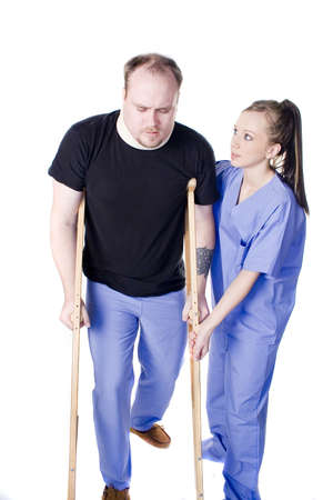 medical condition: Young physical therapist helping injured man with crutches