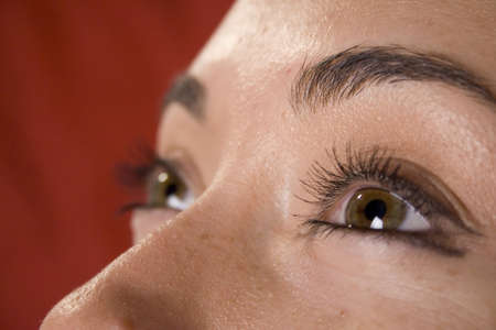 dilate: Close up of womans eyes on red background