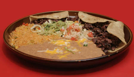 tast: Plate of tast mexican food tacos with rice and beans