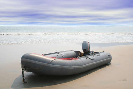 Beached inflatable boat with ocean waves in background