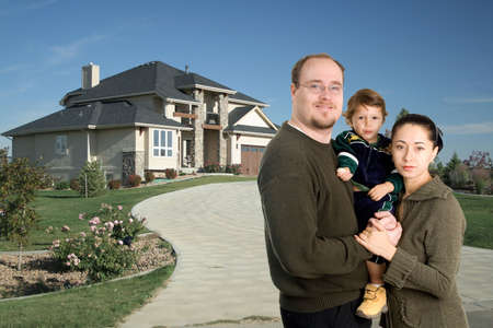 Young family standing together in front of luxury home photo