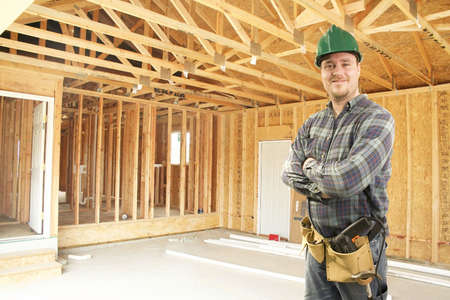 Construction worker standing in new home framed garage