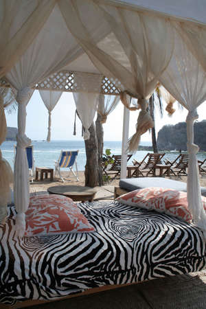 pergola and chairs on beach under palm tree in mexico photo