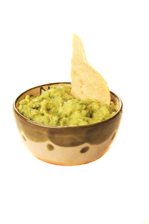 guacamole: A bowl of guacamole with a chip