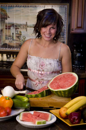 A young woman cutting watermellon in the kitchen photo