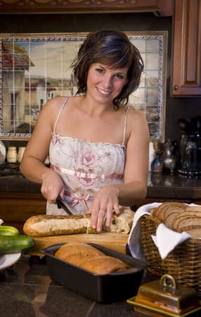 A young woman in the kitchen cutting bread Stock Photo - 3747210