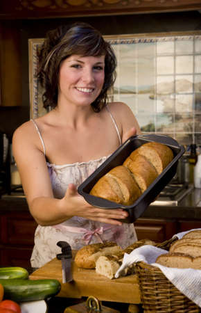 A cute young woman baking bread in kitchen Stock Photo - 3747217