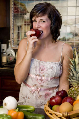 A pretty young woman taking a bite out of an apple photo