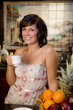 A young woman in the kitchen drinking coffee Stock Photo - 3747204