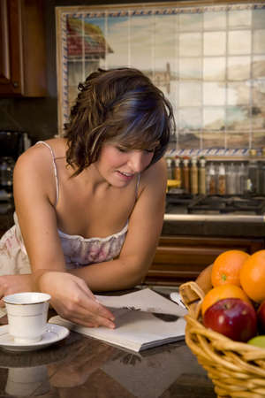 A young woman in the kitchen reading a magazine and drinking coffee photo