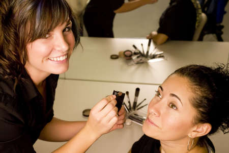 A young make up artist applying make up to a pretty young woman