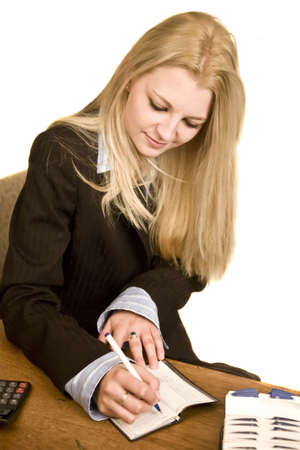 person writing: A young woman balancing her check book Stock Photo