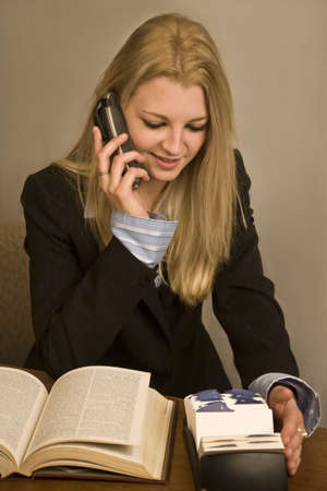 rolodex: A young business woman talking on phone searching a Rolodex