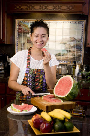 A young woman cutting and eating watermelon in the kitchen photo
