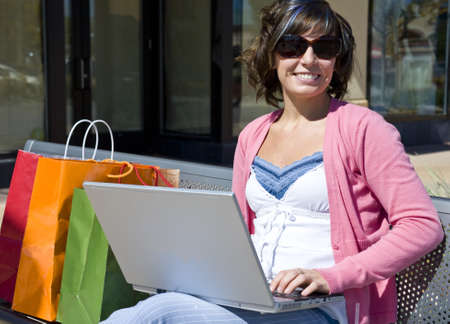 A young woman shopping sitting on her computer with bags Stock Photo