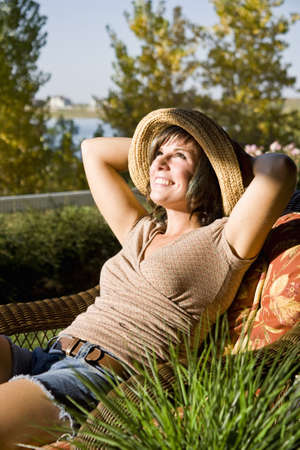 Woman sitting on a patio chair relaxing at home by the lake