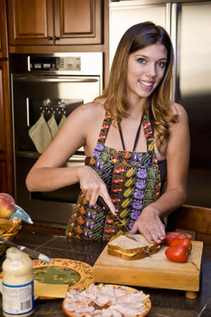 peanut butter and jelly: young woman in kitchen making sandwiches smiling