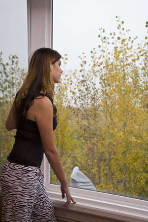 looking out: Young woman standing next to and looking out the window