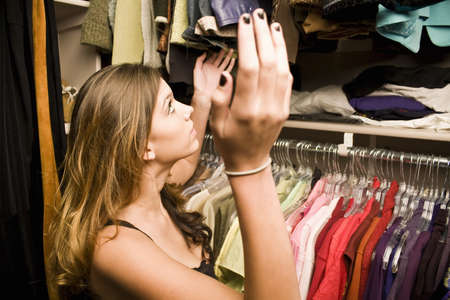 clothes organizer: Young woman frustrated looking through her closet trying to find clothes Stock Photo