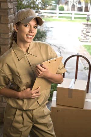 facteur: Jeune femme d'exp�dition ou la livraison colis � la porte Banque d'images