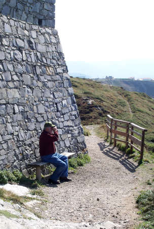 spaniard: A tourist sitting on an overlook bench at a ancient spaniard castle on the northern coast Stock Photo