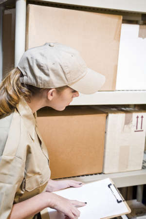 inventories: A young worker taking inventory in a warehouse