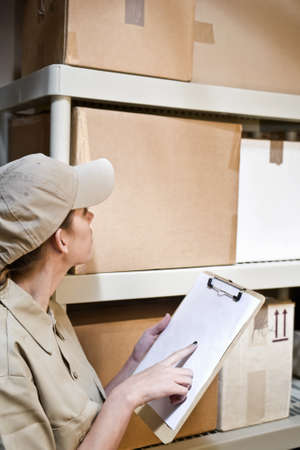 inventario: Un joven trabajador de almac�n teniendo inventario