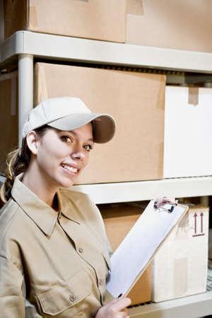 inventario: Mujer joven en el suministro de habitaci�n teniendo inventario Foto de archivo